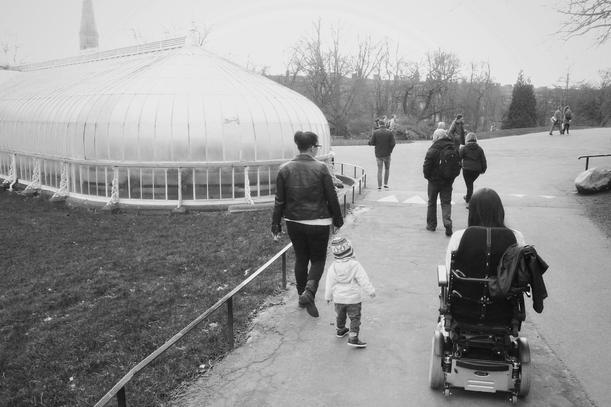 Emma in her power wheelchair, her sister and nephew walking beside her. They have their backs to the camera heading towards the Glasgow Botanic Gardens in the background.