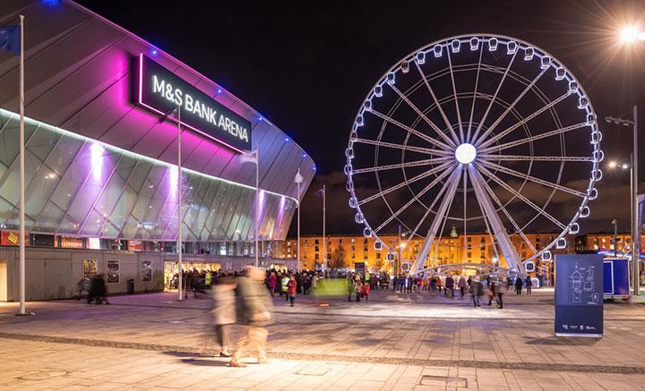 An exterior shot of the arena lit up at night with the ferris wheel beside it.