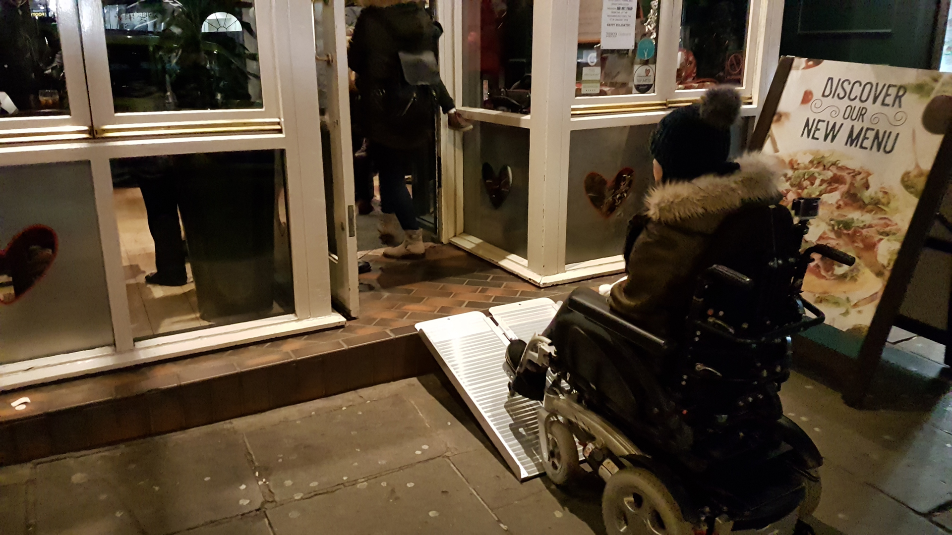 Wheelchair user entering Bella Italia Hanover Street restaurant via a portable wheelchair ramp during Edinburgh's Christmas.