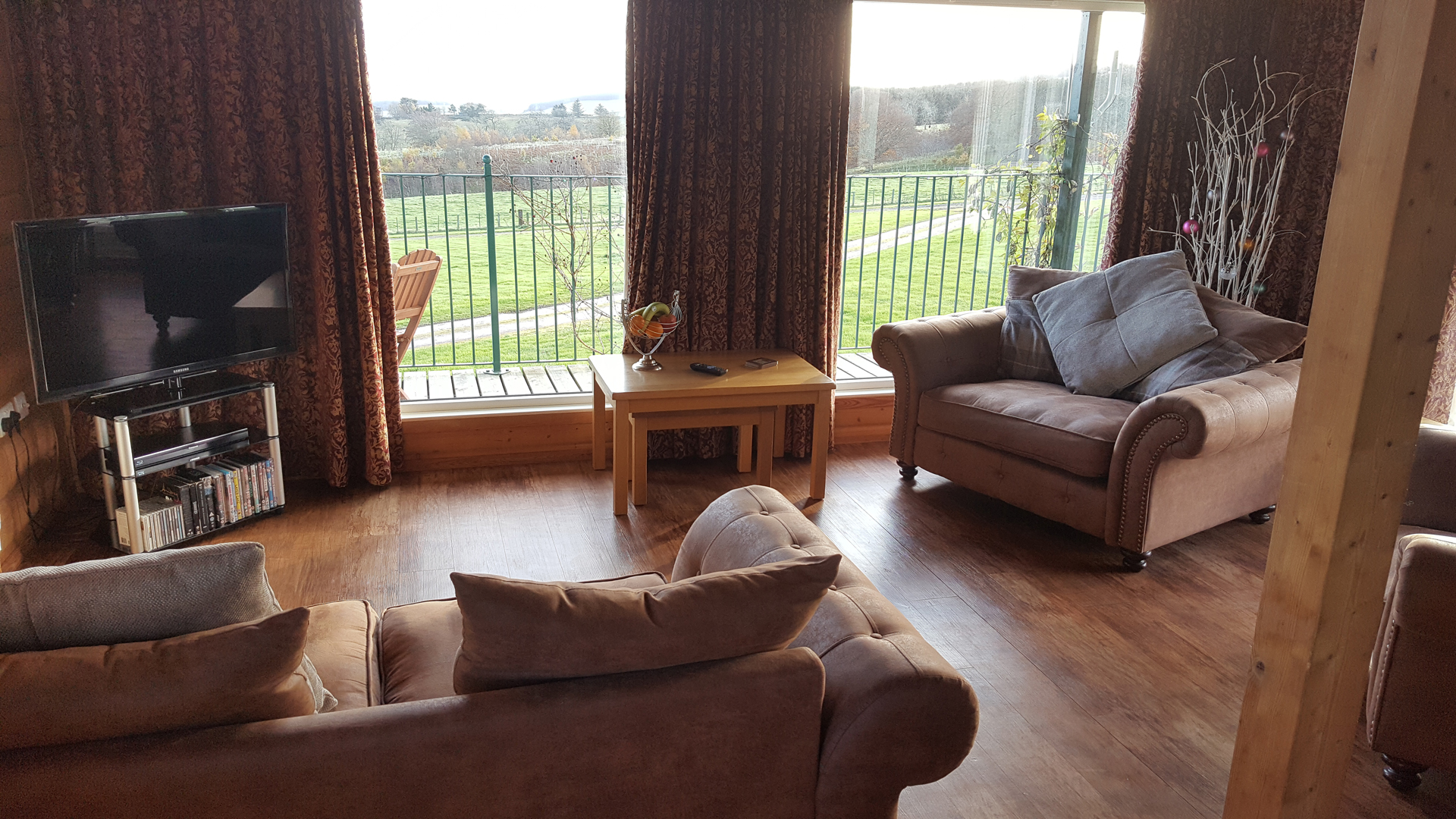 The living area with view out the large windows in The Ramsay at Airhouses Luxury Self Catering Lodges in Scottish Borders