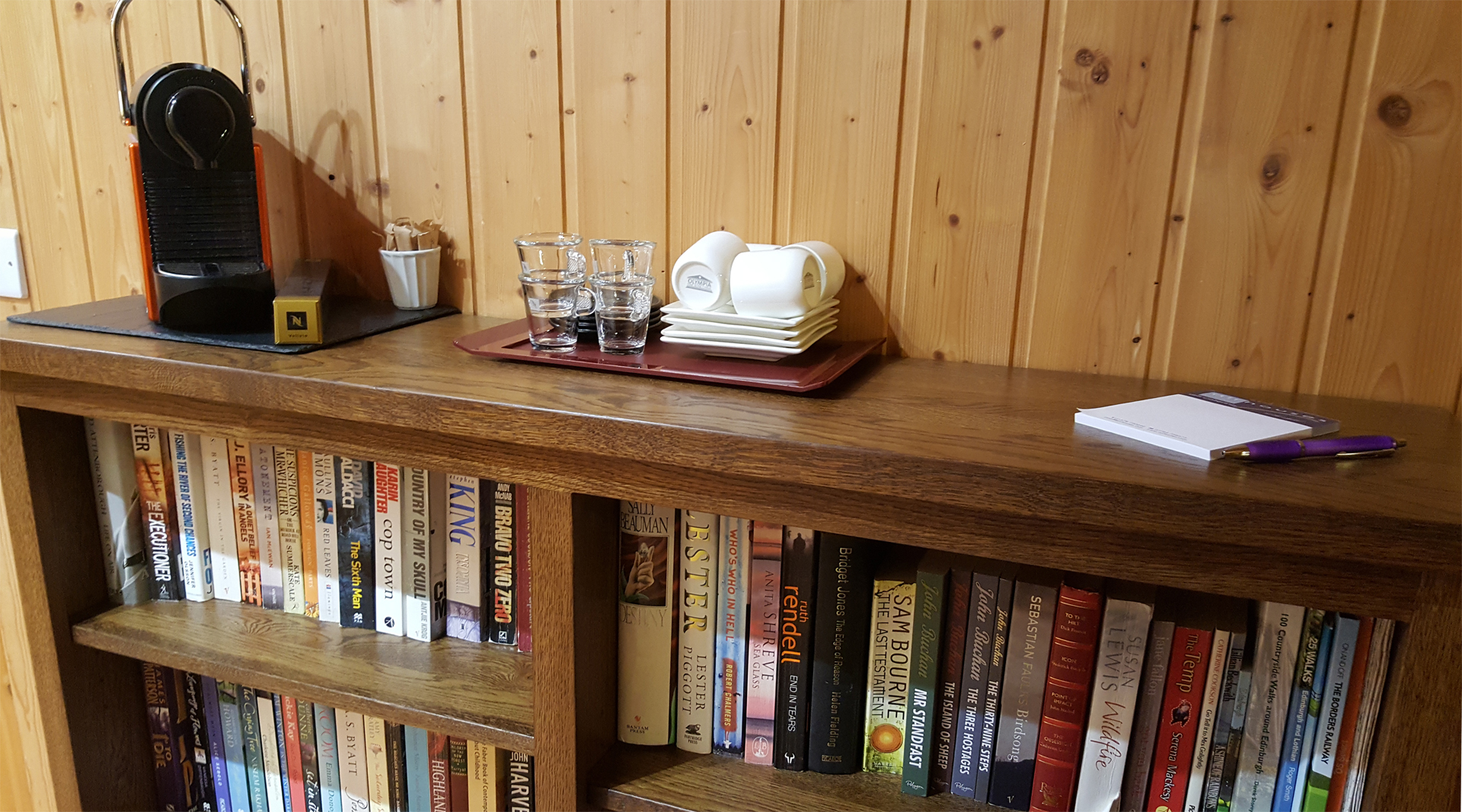 Book shelf with coffee marker on top in the hallway of The Ramsay lodge at Airhouses Luxury Self Catering Lodges in Scottish Borders