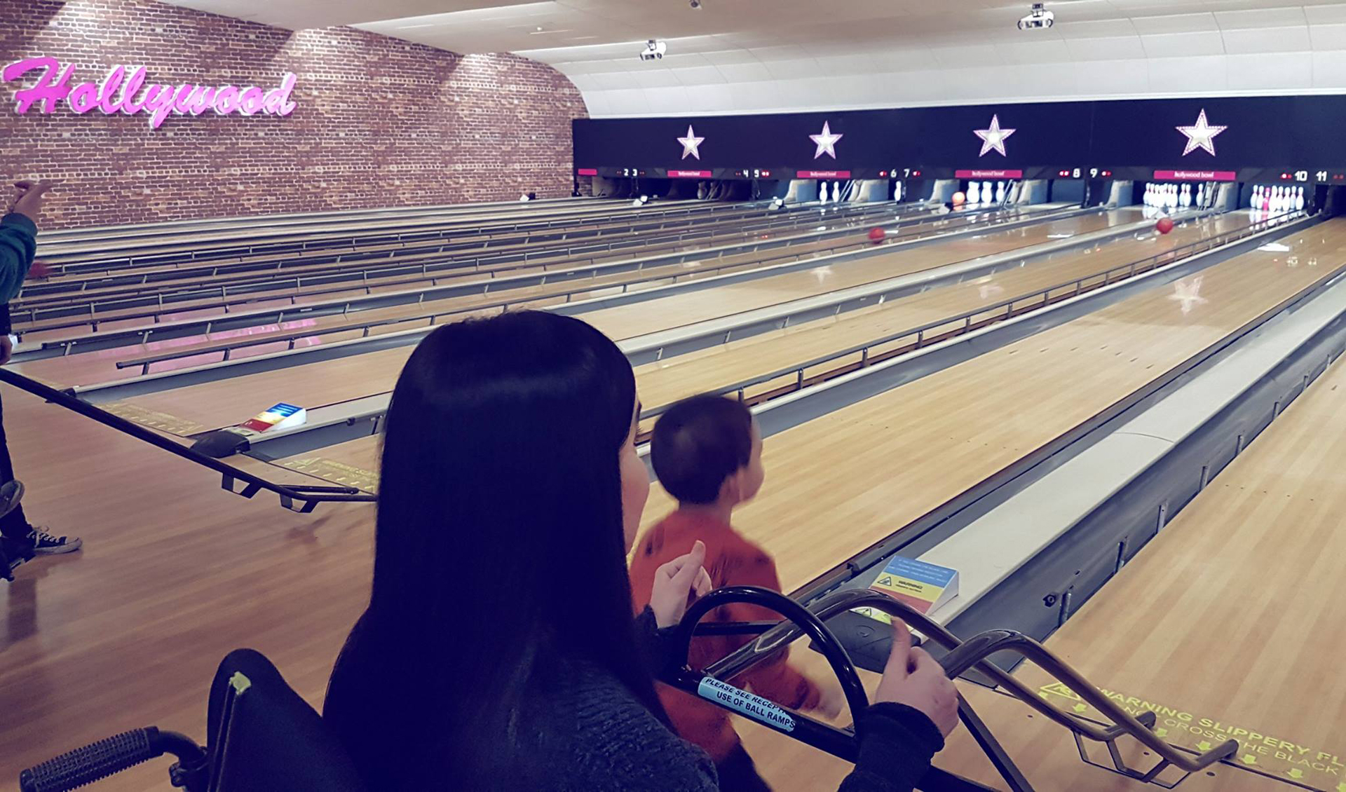 Emma of Simply Emma at ten pin bowling with her nephew using a ramp for the bowling balls.