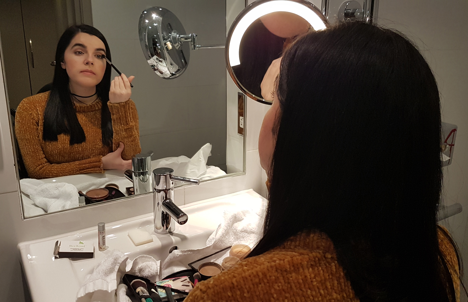 Emma of Simply Emma doing her makeup in her hotel room wearing a mustard chenille jumper.
