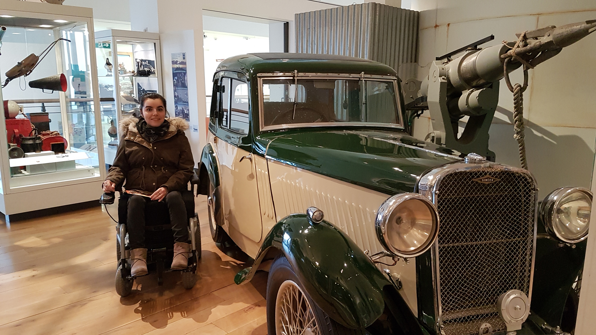 Emma sitting beside a old car at one of the exhibits at Shetland Museum and Archives