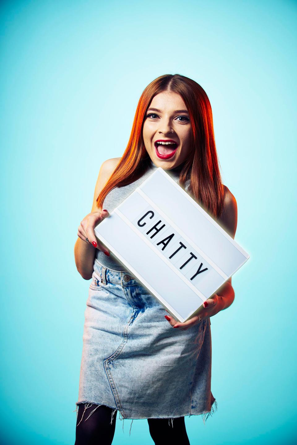 Becky Dann of The Undateables stands holiding a sign with the word 'Chatty'