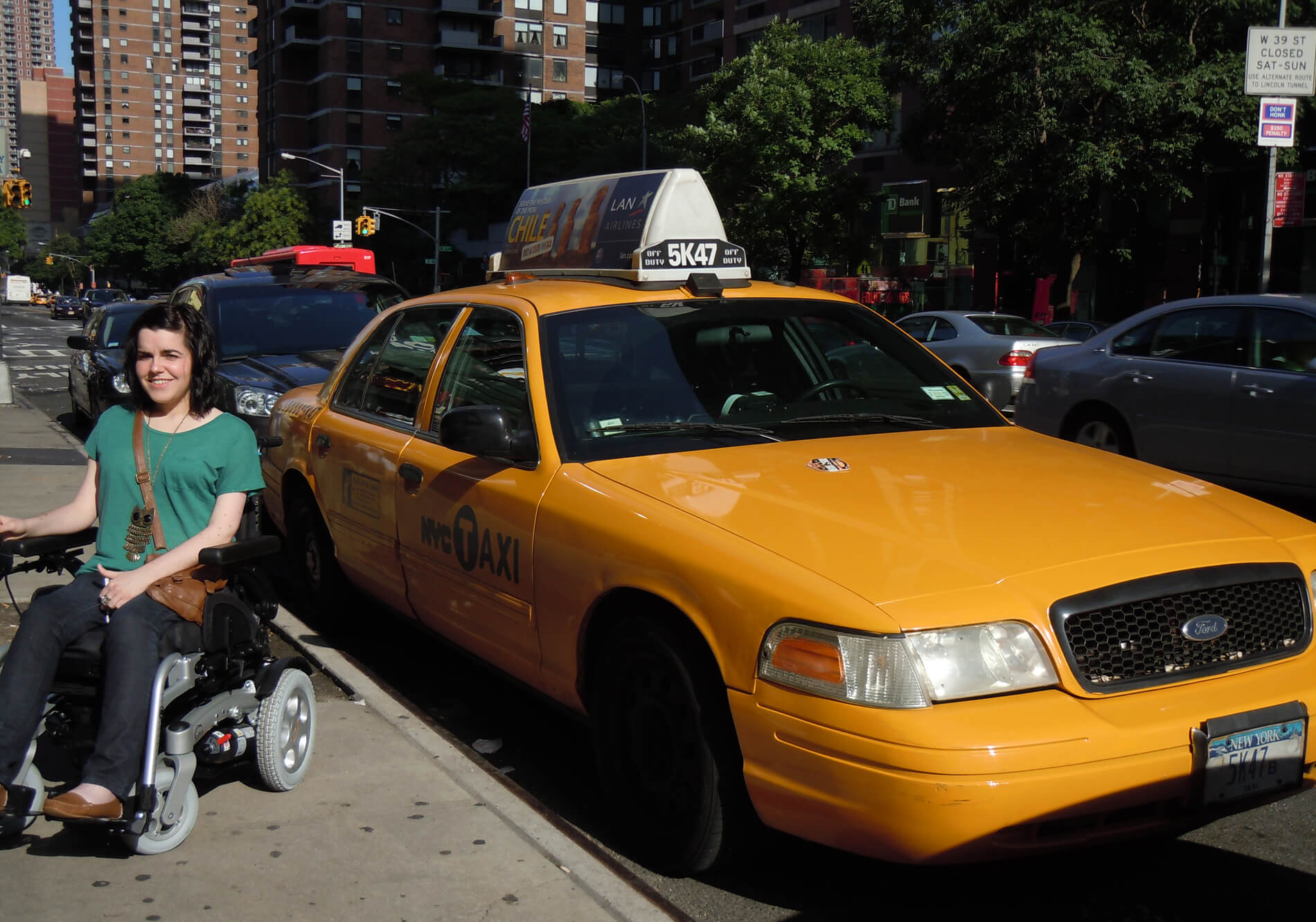 Emma in her power wheelchair sitting beside a yellow New York City taxi cab: Ask Me Anything Q&A Part 1