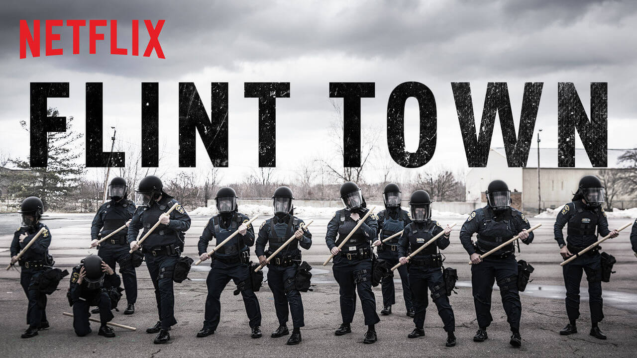 Flint Town the netflix docu-series poster with police officers standing with their riot gear on.