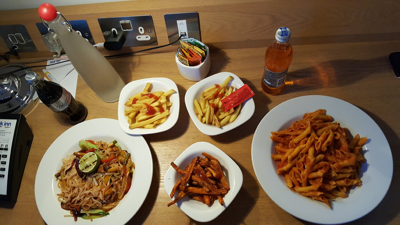 Stir fry noodles with tofu, tomato pasta and fries with drinks ordered from hotel room service.