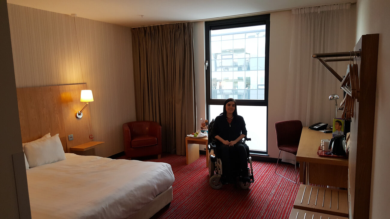 Emma sitting in her wheelchair accessible hotel room at Park Inn by Radisson Aberdeen