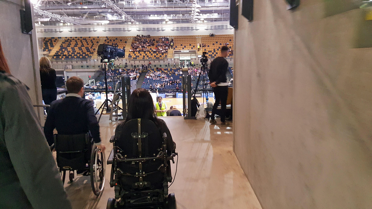 Emma and Ryan entering the basketball viewing arena in their wheelchairs : wheelchair access at Emirates Arena