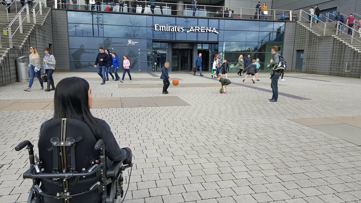 Emma sitting in her wheelchair outside the entrance of the Emirates Arena before the Glasgow Rocks Basketball Match: wheelchair access at Emirates Arena