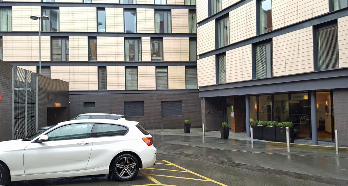 Entrance exterior of Staybridge Suites Newcastle with hotel carpark close by