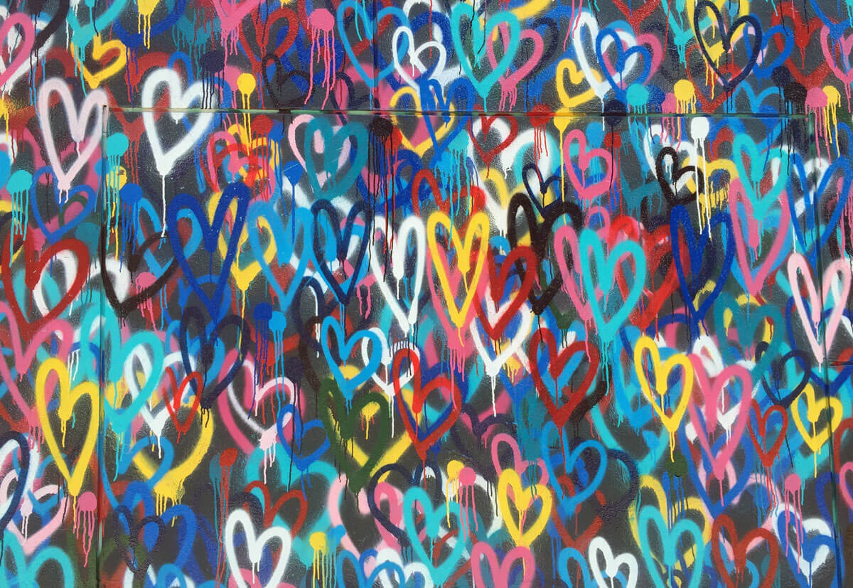 A wall covered in graffiti love hearts.