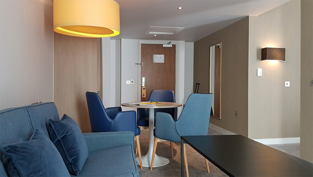 Holiday Inn Manchester City Centre Wheelchair Access Review - living area lounge in wheelchair accessible suite with dining table and sofabed