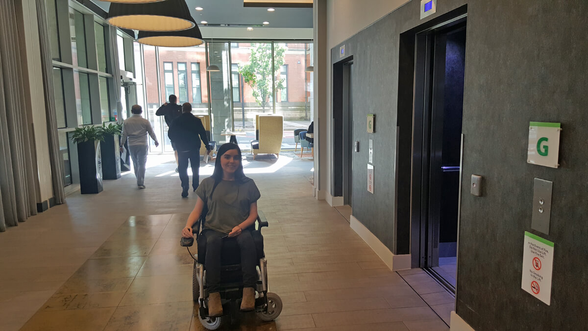 Holiday Inn Manchester City Centre Wheelchair Access Review - Emma sitting in the lobby waiting for the lift to take her to her wheelchair accessible suite.