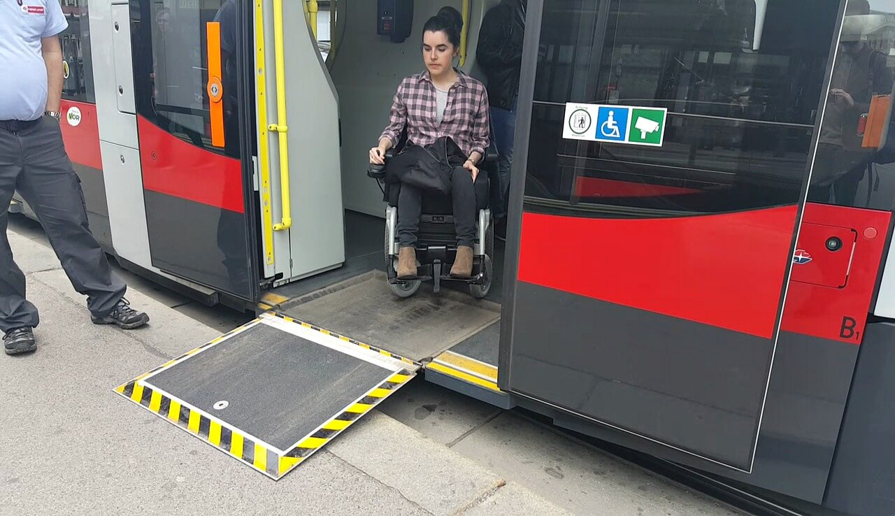 Emma in her wheelchair exiting a wheelchair accessible tram in Vienna
