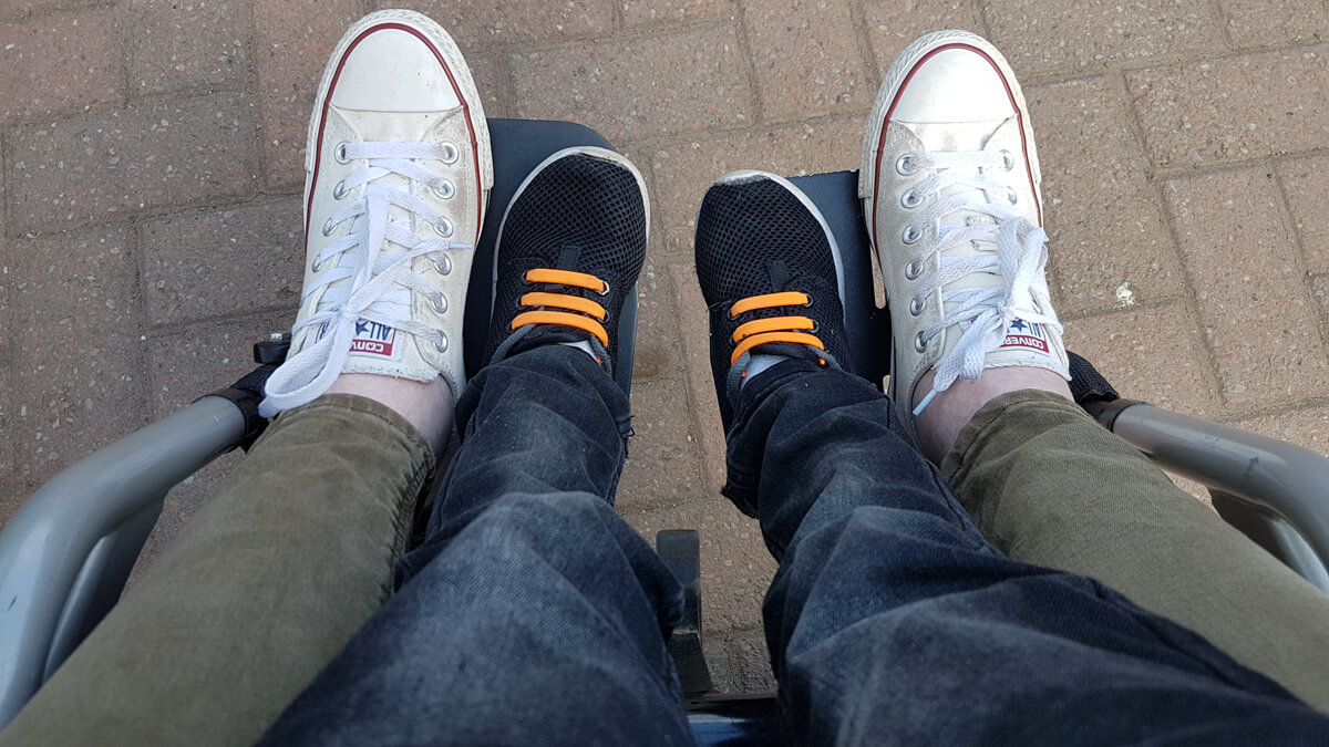 Things-I've-loved-in-May: A photo of mine and my nephews legs and feet on my wheelchair footplates. Photo taken by my nephew.