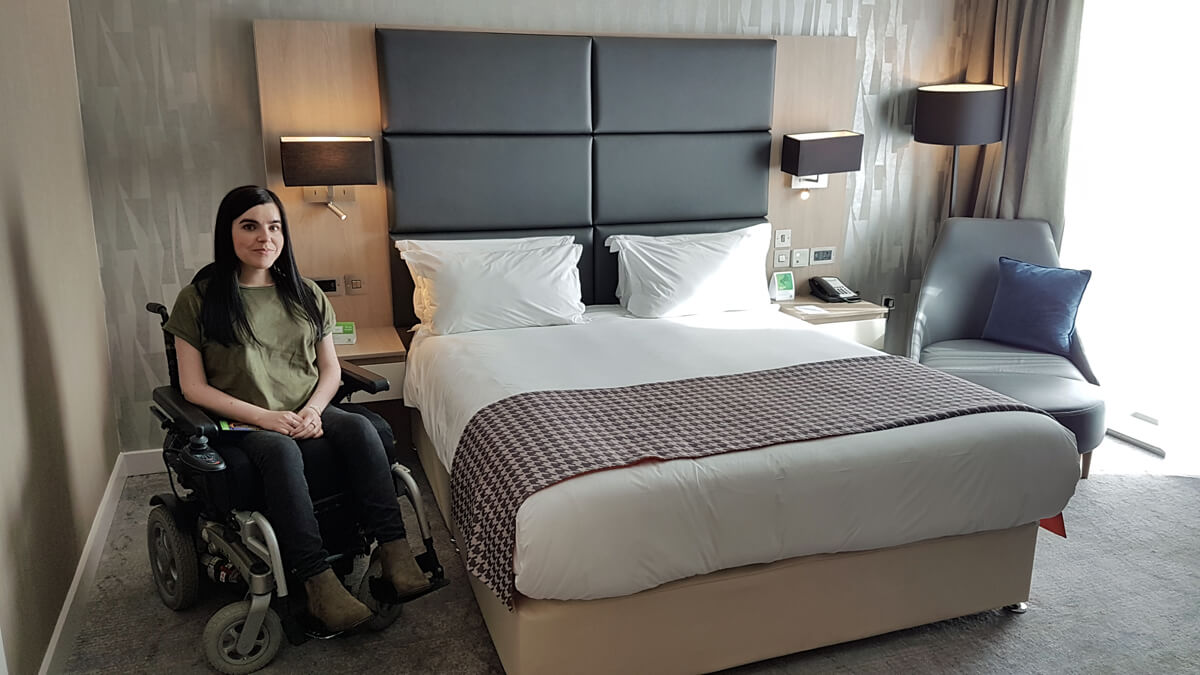 Things-I've-loved-in-May: Emma sitting beside the bed in the wheelchair accessible suite at Holiday Inn Manchester City Centre.