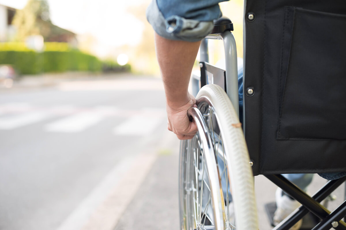 Wheelchair Access and Disability Mediation: A close up shot of a mans arm self-propelling his wheelchair.