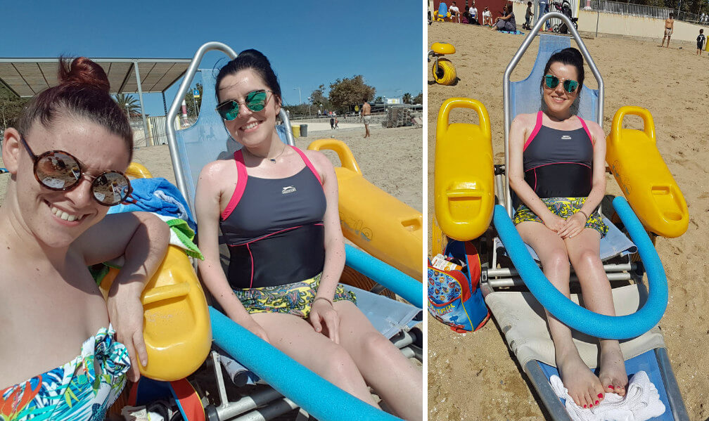 Emma sitting in accessible beach wheelchair on the sand with her sister on nova icaria beach in Barcelona.