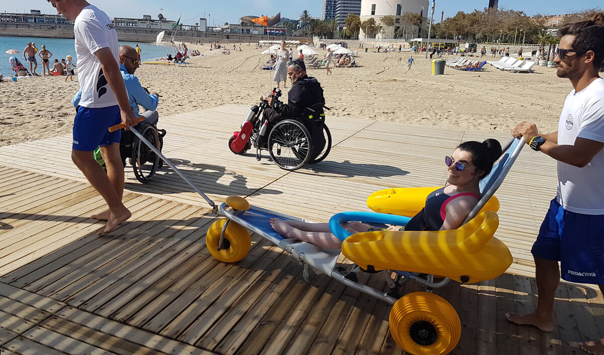 Emma sitting in accessible beach wheelchair being wheeled along an accessible wooden path across the sand and into the sea by volunteer service lifeguards on nova icaria beach in Barcelona.