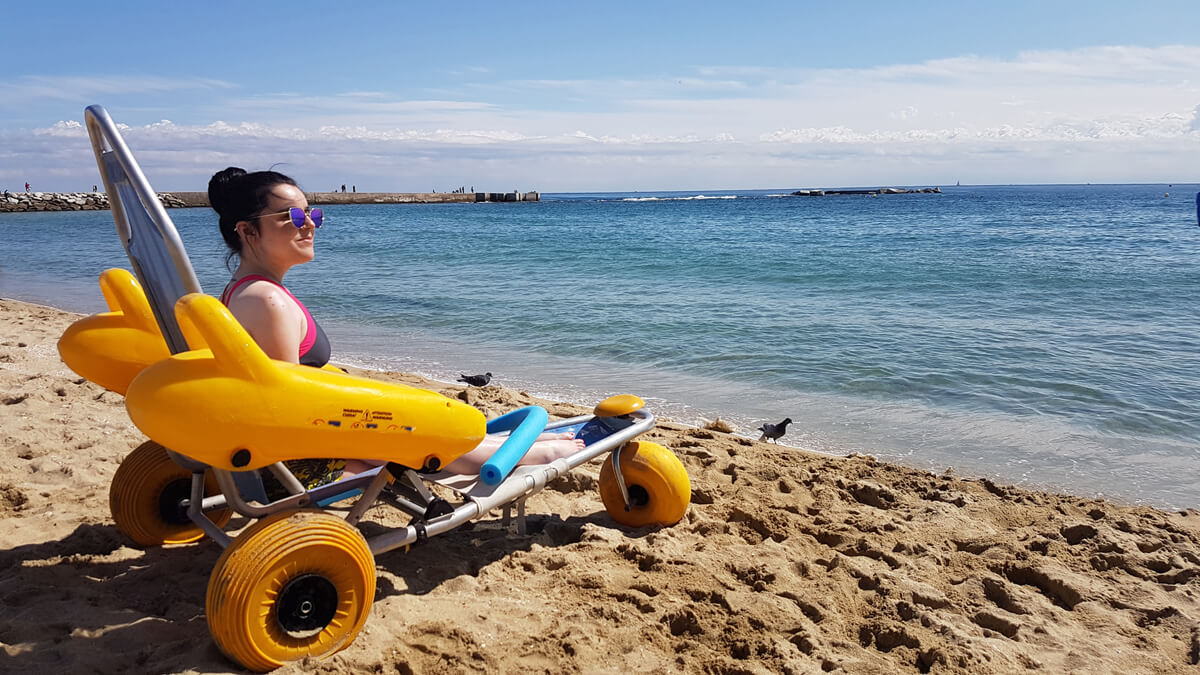 Emma sitting in an accessible beach wheelchair on nova icaria beach in Barcelona. Emma is looking across the sea admiring the view.