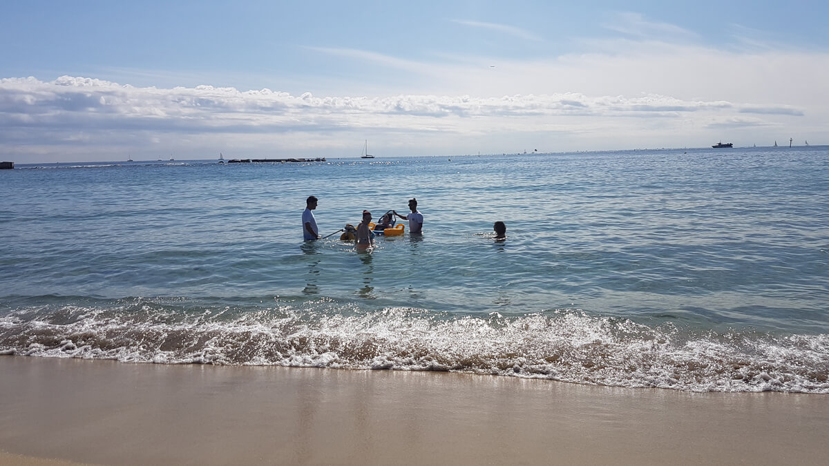 Emma sitting in accessible beach wheelchair in the ocean with the volunteer service lifeguards and her sister on nova icaria beach in Barcelona.