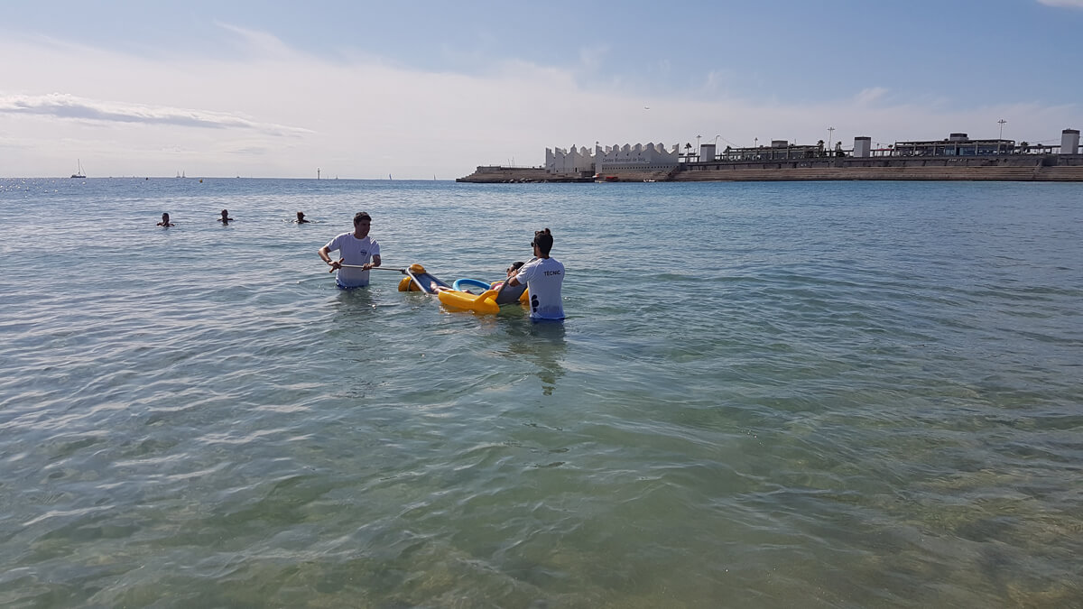 Emma entering the water in accessible beach wheelchair by volunteer service lifeguards on nova icaria beach in Barcelona.