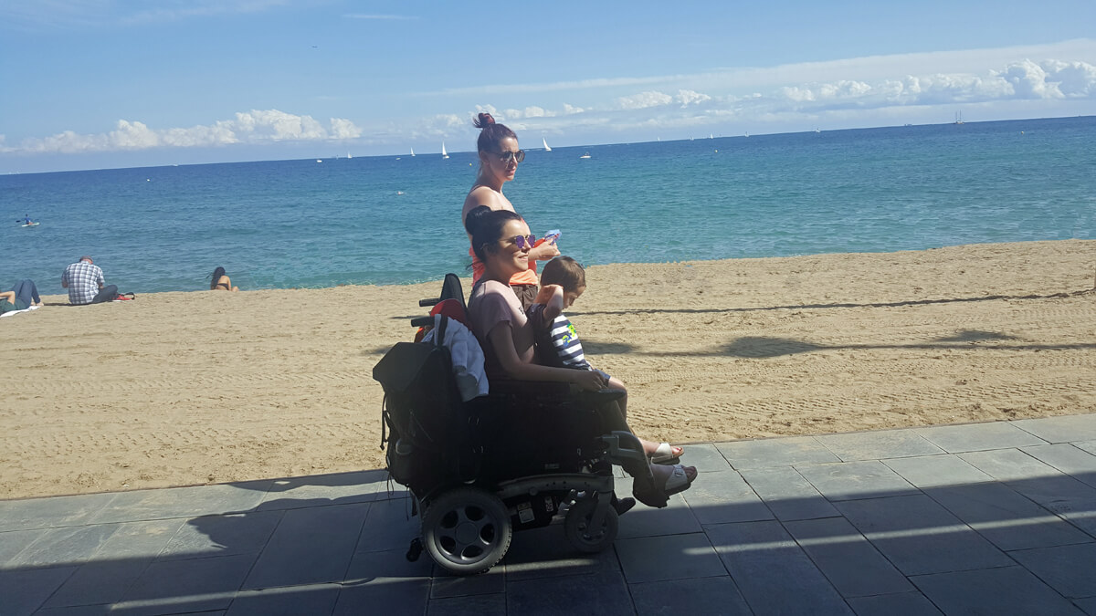 Emma in her wheelchair riding along the beach promenade in Barcelona with her nephew sitting on her lap and her sister walking along beside her.