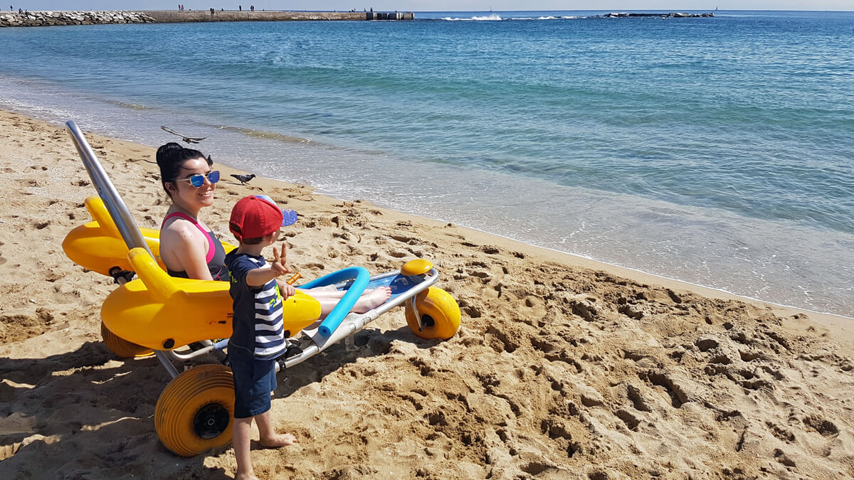 Emma sitting in a beach wheelchair on nova icaria beach in barcelona with her nephew.