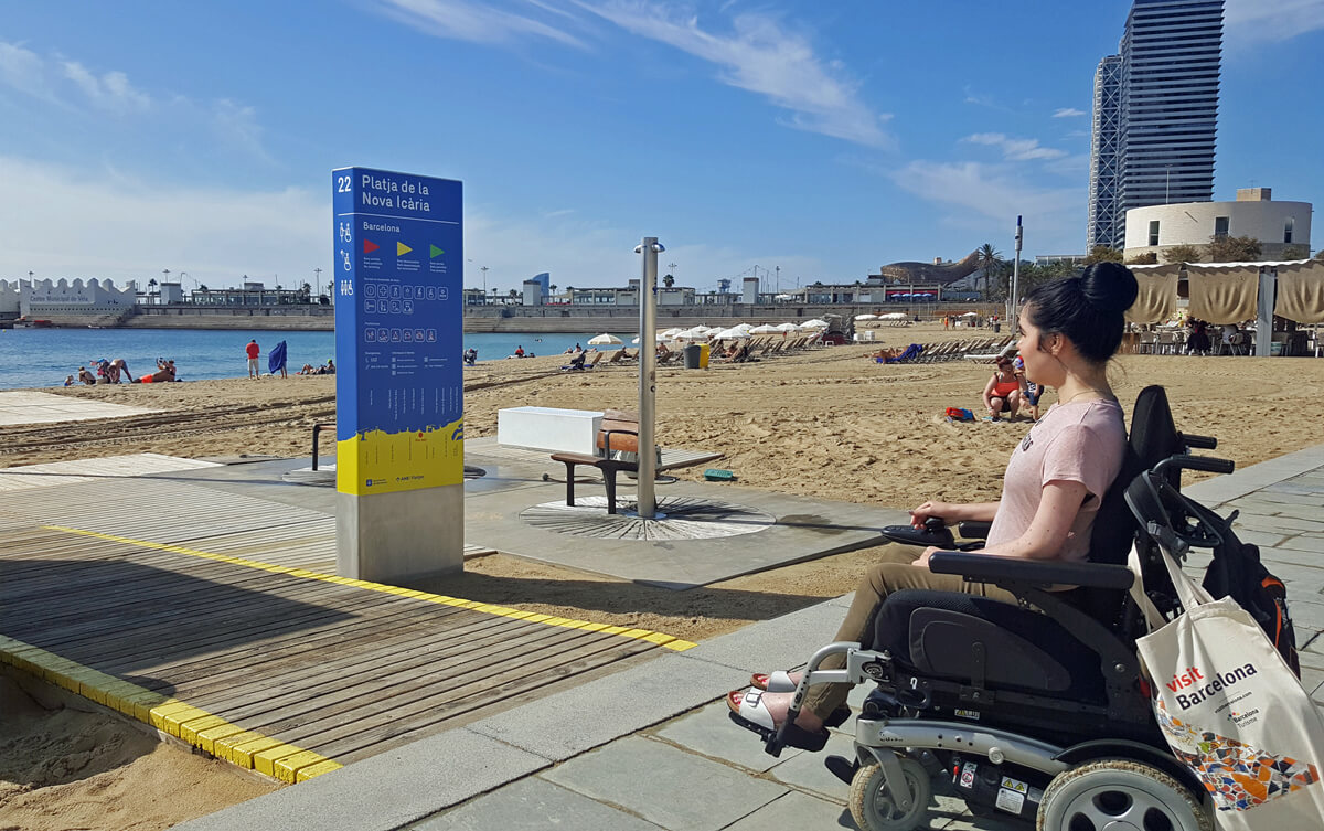 Emma sitting in her wheelchair beside a wheelchair accessible wooden path on the promenade on Nova Icaria beach in Barcelona.