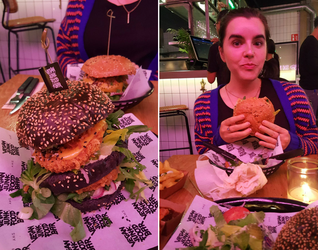 Emma enjoying a vegan burger at Vegan Junk Food Bar in Amsterdam. Emma is wearing a blue and orange striped cardigan.