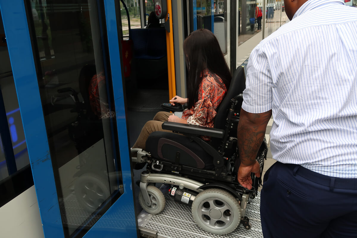 Emma boarding a tram via a portable wheelchair ramp in Amsterdam.