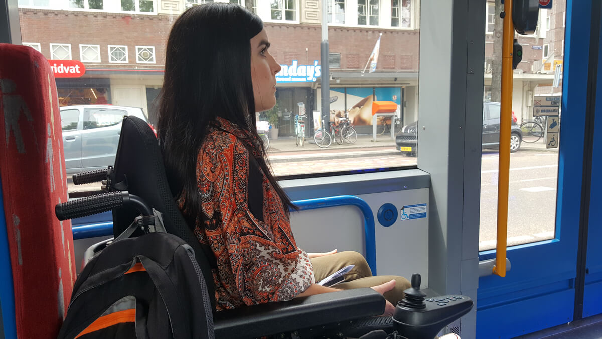 Emma sitting in her wheelchair on board a tram in Amsterdam.