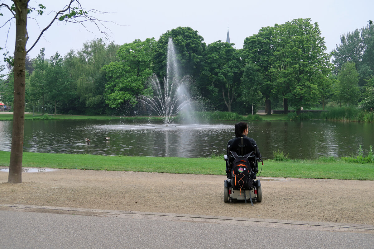 Emma sitting in her wheelchair while looking over the pond and admiring the water fountain in Vondelpark, Amsterdam.