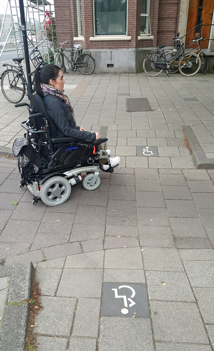 Emma crossing a road in Amsterdam and using the wheelchair accessible lowered curb cuts to drive onto the pavement.