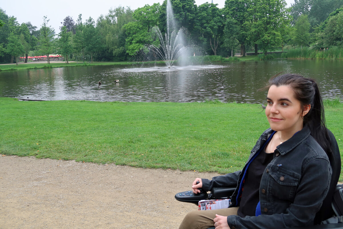 Emma sitting in her wheelchair with the pond and water fountain in the background in Vondelpark, Amsterdam.