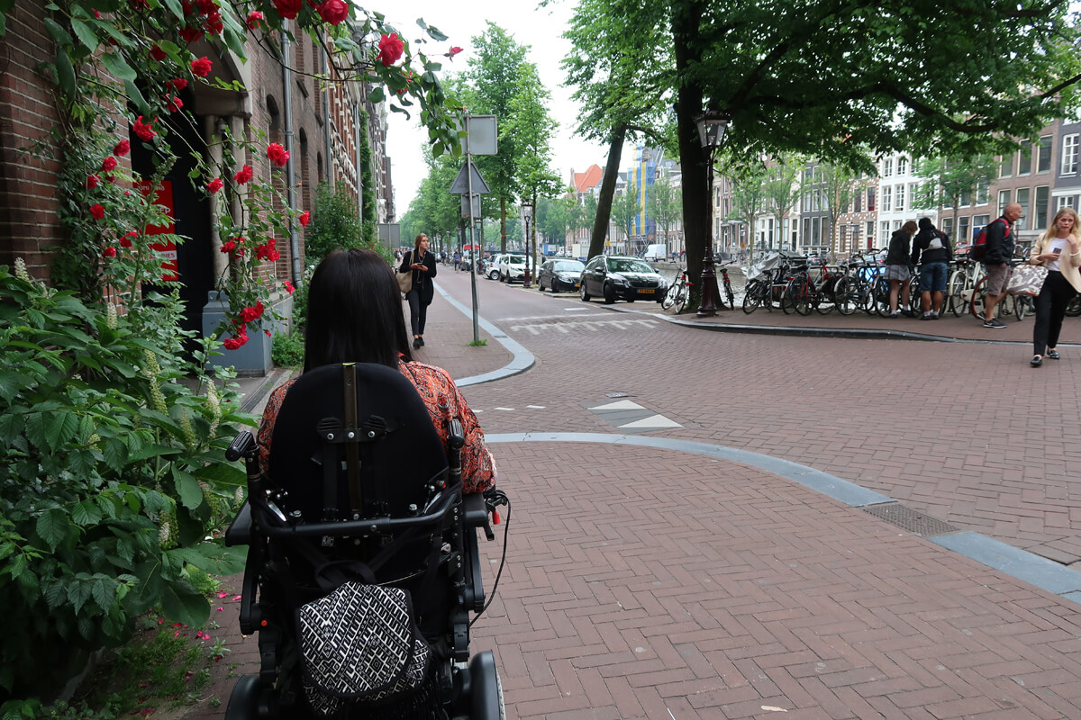 Emma driving her powered wheelchair through the quiet quaint streets of Amsterdam.