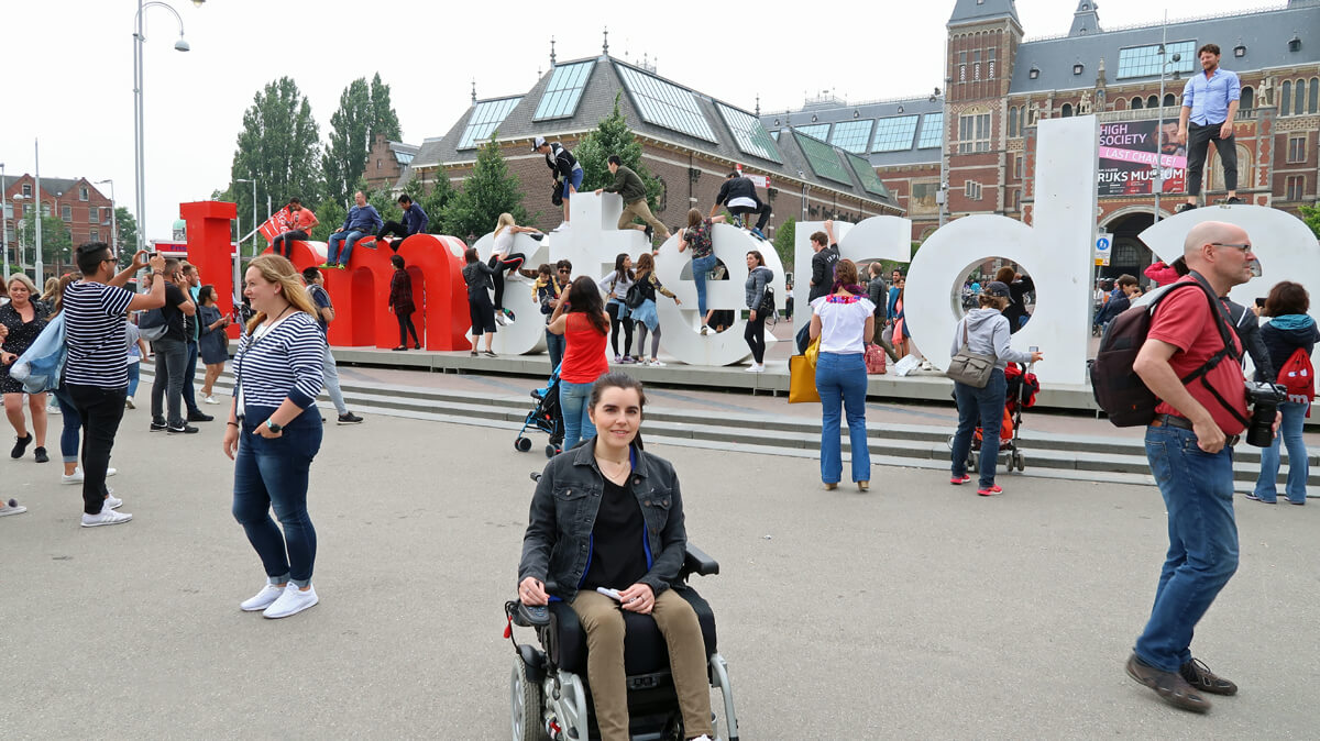 Emma sitting in her wheelchair next to the huge iAmsterdam sign in Museumplein, Amsterdam.