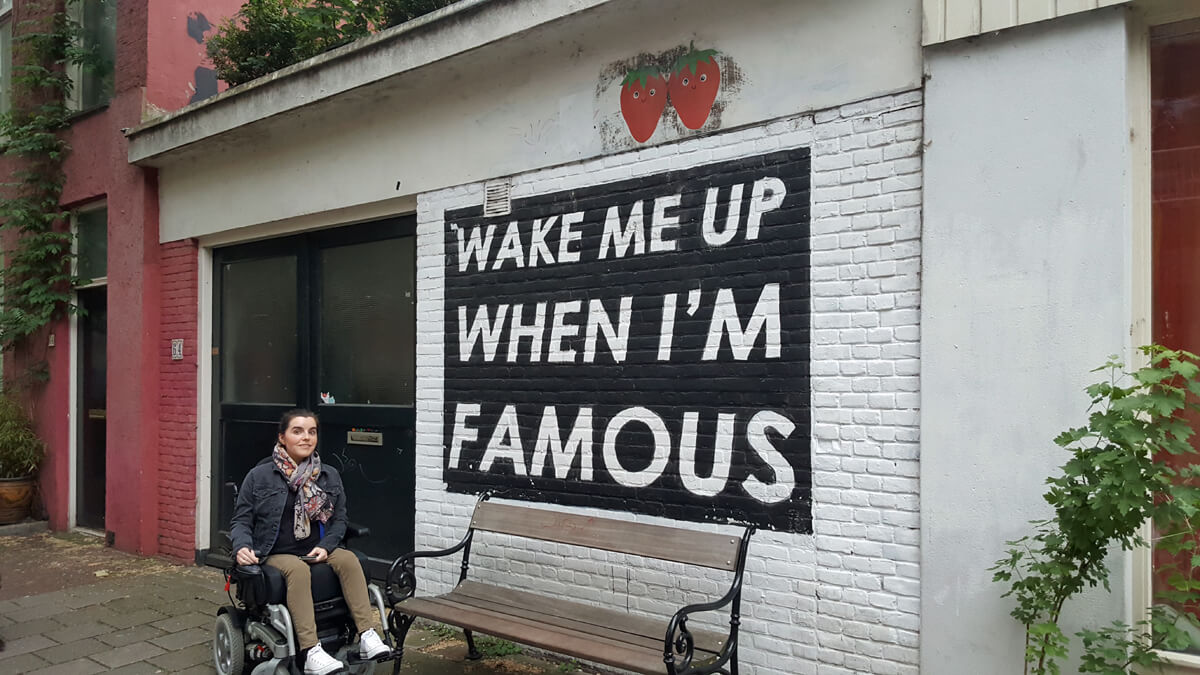 Emma sitting next to the 'Wake me up when I'm famous' bench in De Pijp, Amsterdam.