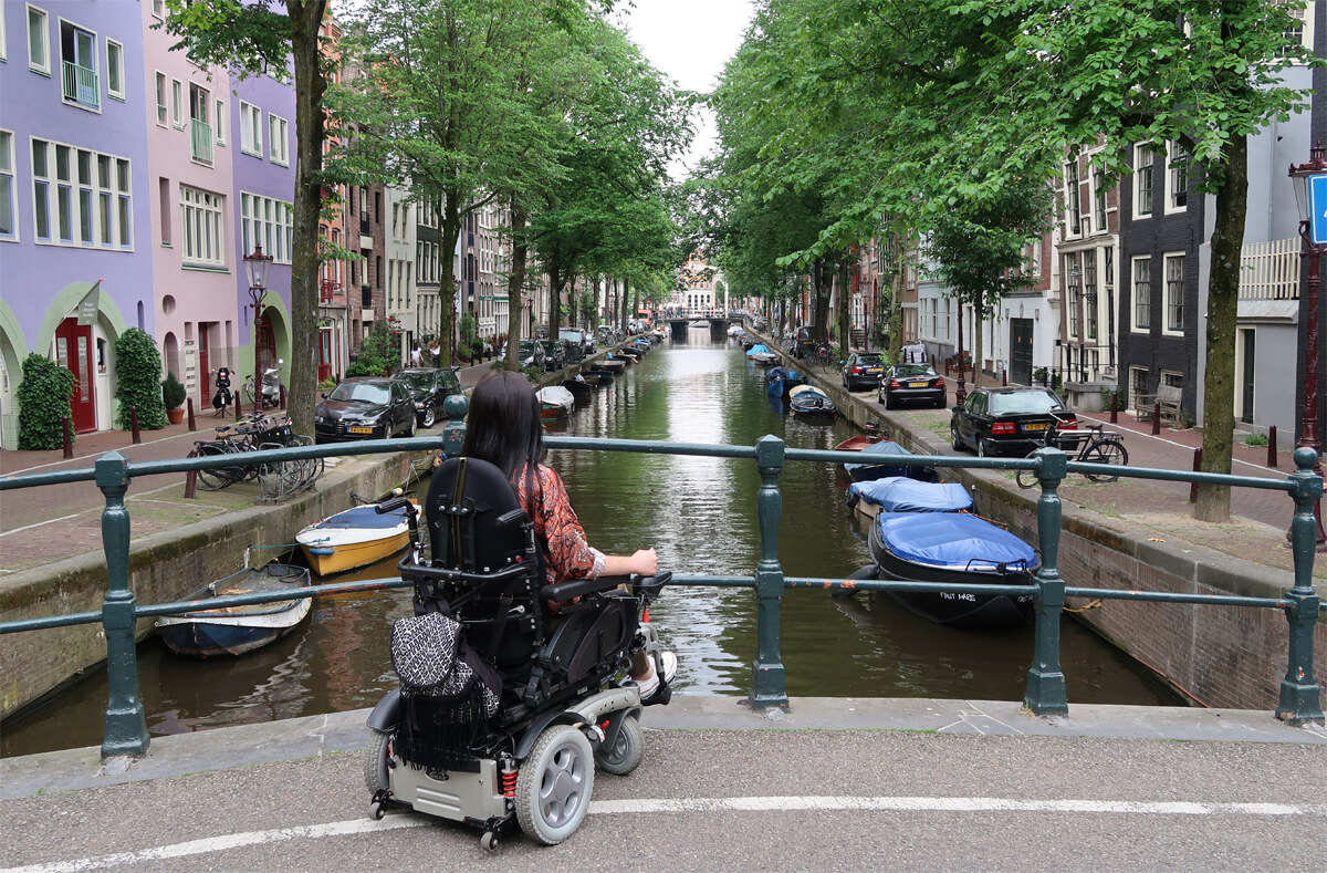 Emma sitting in her wheelchair on a canal bridge in Amsterdam. There are a line of colourful buildings down each side of the canal.