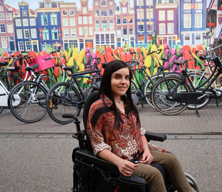 3 Days In Amsterdam A Wheelchair Users Travel Guide to Amsterdam: Emma sitting outside the bloemenmarkt with a tulip wall mural behind her and a row of bikes.