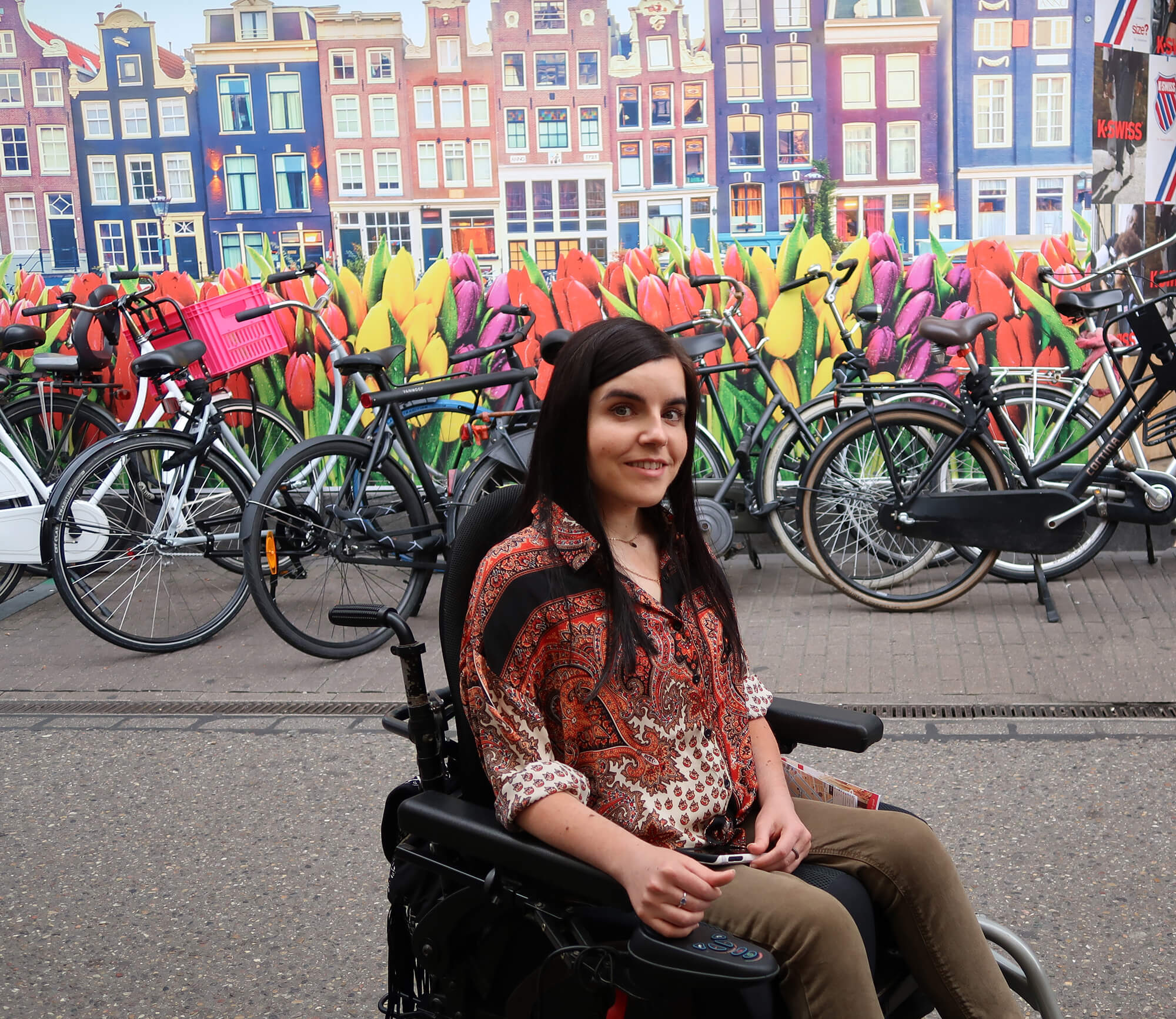 Emma sitting outside the bloemenmarkt with a tulip wall mural behind her and a row of bikes.