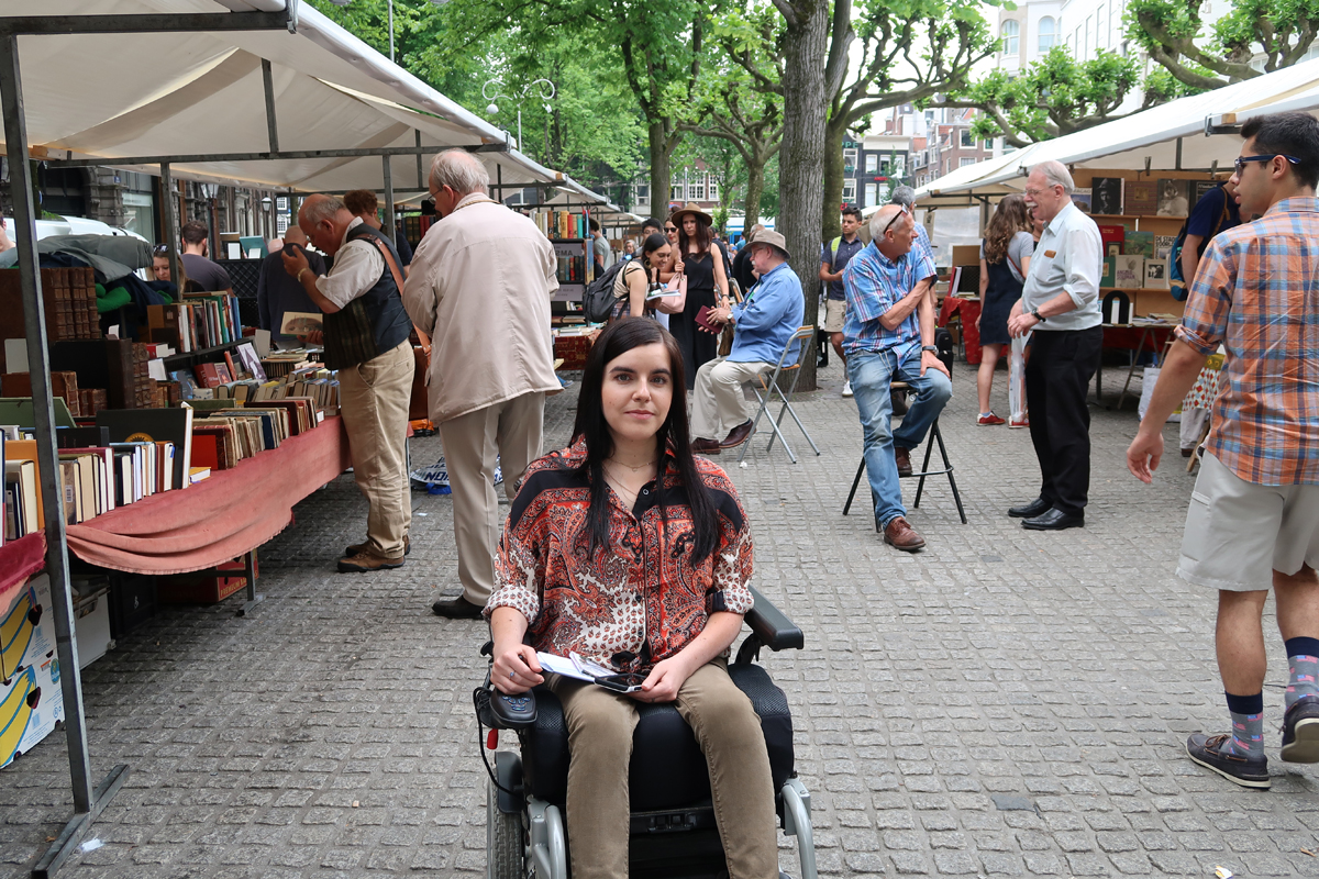 Emma sitting in her wheelchair in the middle of the book market at Spui Square in Amsterdam.