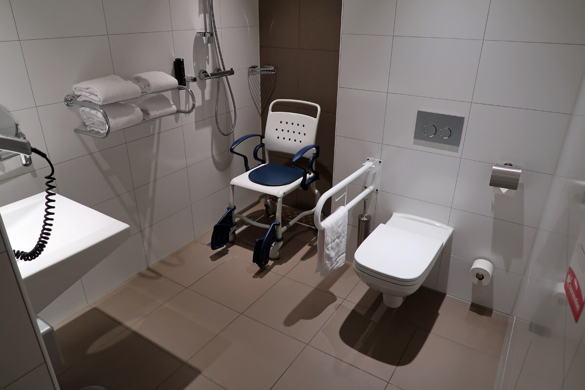 Corendon Vitality Hotel Amsterdam Wheelchair Accessible Hotel In Amsterdam: Roll-in shower with shower chair and toilet with grab bar.