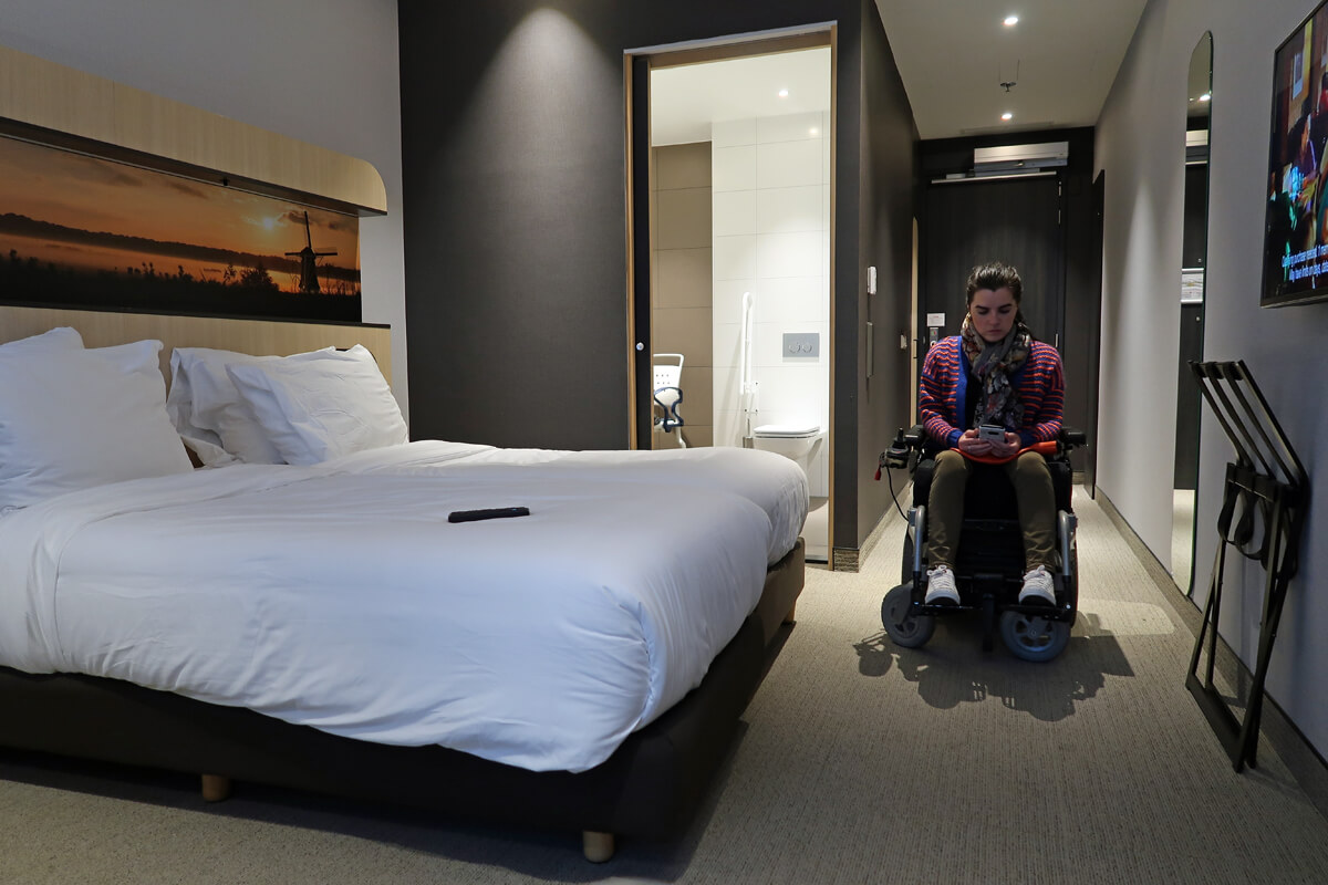 Corendon Vitality Hotel Amsterdam Wheelchair Accessible Hotel In Amsterdam: Emma sitting in her powered wheelchair looking at her phone. She is in her wheelchair accessible hotel room at Corendon Vitality Hotel Amsterdam.