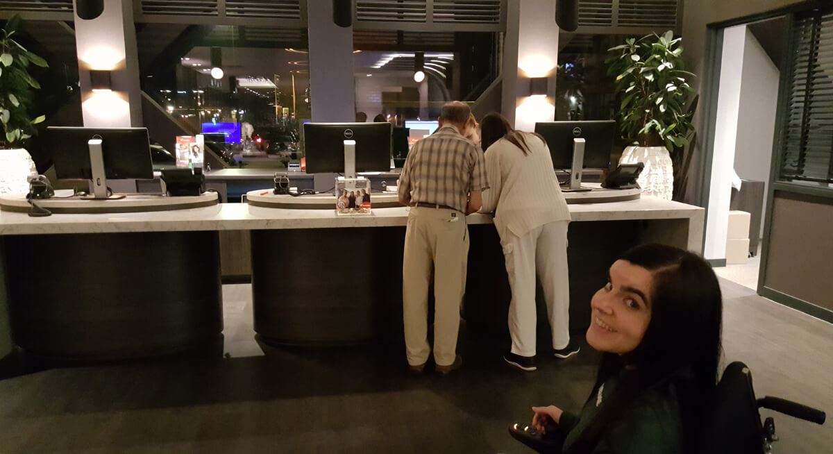 Corendon Vitality Hotel Amsterdam Wheelchair Accessible Hotel In Amsterdam: Emma smiling at the camera while checking in at Corendon Vitality hotel Amsterdam at 1am.