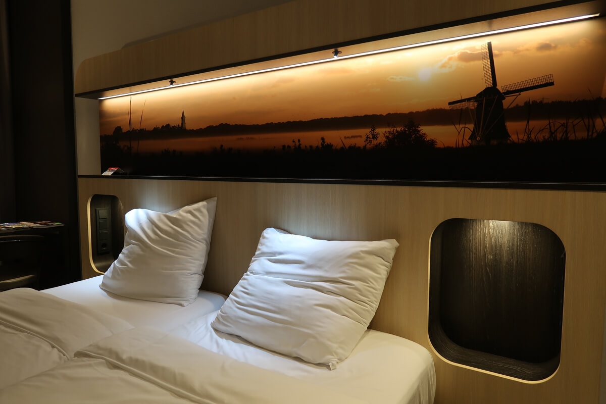 Corendon Vitality Hotel Amsterdam Wheelchair Accessible Hotel In Amsterdam: Comfortable bed with inbuilt headboard showing a silhouette sunset photo of a windmill in field in Amsterdam.