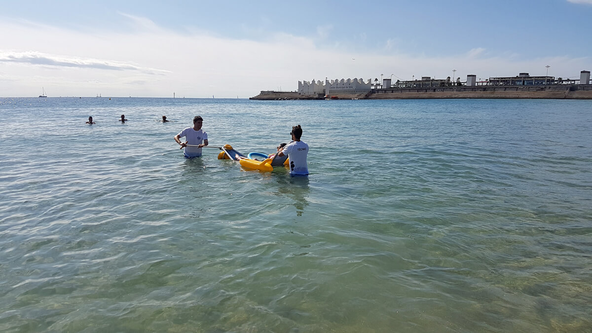Favourite Accessible Things To Do In Barcelona: Emma in a beach wheelchair in the ocean with the help of two male volunteers from the assistive bathing service on Nova Icària Beach Barcelona.