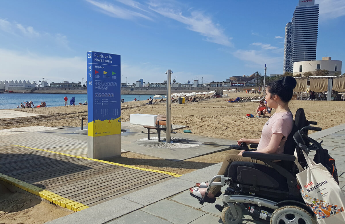 Favourite Accessible Things To Do In Barcelona: Emma sitting in her powered wheelchair looking across the beach.